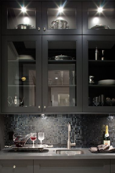 source: Kelly Deck Design Glossy black butler's pantry with glass-front kitchen cabinets, gray quartz countertops and glossy black glass tiles backsplash.