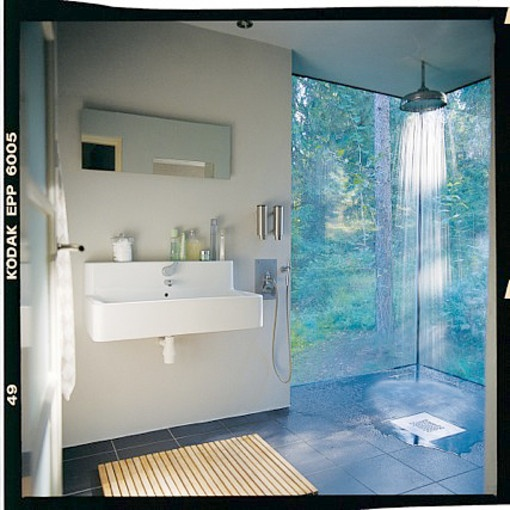 Defined by two walls of glass, the shower in this Swedish bathroom captures the feel of bathing outdoors yearround.