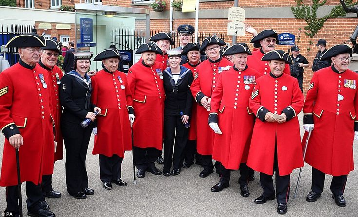 Veterans: A group of crimson coated Chelsea pensioners pose with current members of the Armed Forces outside the Royal Enclosure at Ascot