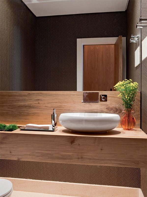 """""""Com estampa que remete a um desenho tribal, o papel de parede de palha (Empório Beraldin) soma aconchego ao lavabo. No tampo da bancada, recortes acolhem vasos de plantas. Ambiente de Olivia Messa."""" Casa Abril"""