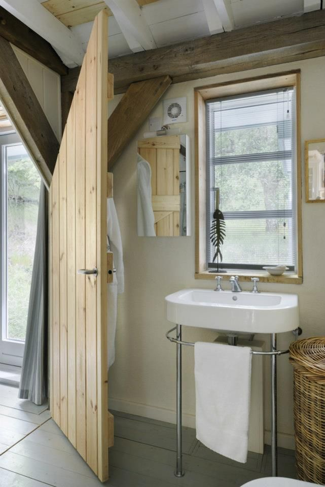 Access to this bathroom is through an interesting door - made to fit around the oak frame. By Roderick James Architects.