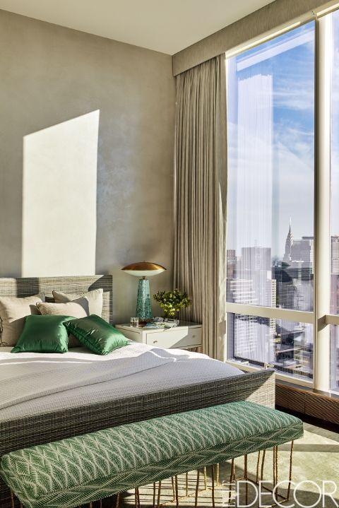 A guest bedroom in this Manhattan apartment offers stunning views and natural lighting.