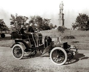Owners of St. Louis Motor Carriage Company, George Dorris (front) and Jesse French Jr. and Sr. in a company racing and touring car built in 1902 or 1903 [in front of Frank P. Blair Statue at northeast corner of Forest Park on Lindell]. Circa 1898-1908.