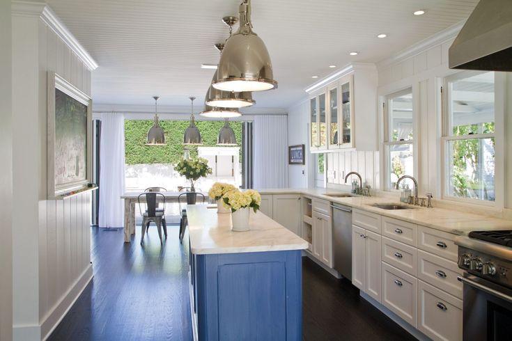 East Hampton beach house kitchen with blue island, aluminum ship fox cargo lights and clean coastal decor.