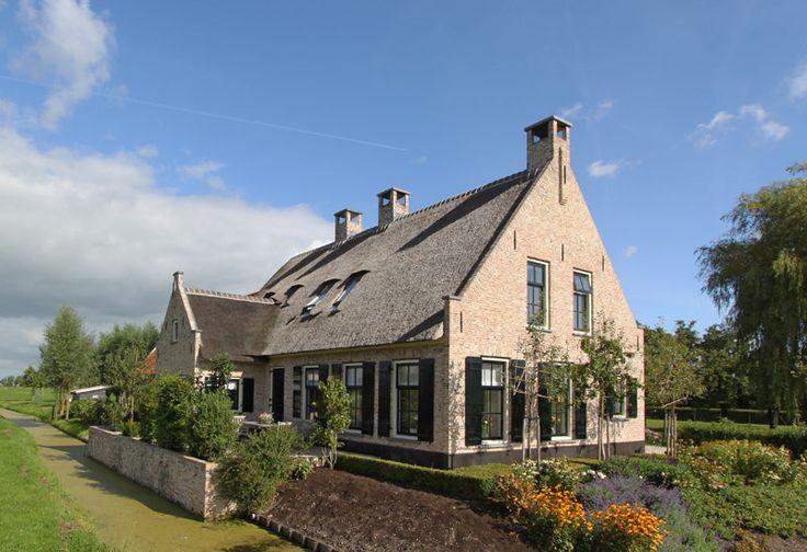 Landelijke woning, uitgevoerd met ijsselsteentjes, luiken en een rieten dak