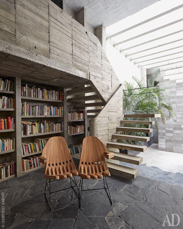 Фрагмент гостиной. Бетонные книжные стеллажи продолжаются на антресоли, куда ведет лестница изтого же материала, отлитая наместе. Два стула напереднем плане — работа хозяина дома Педро Рейеса.