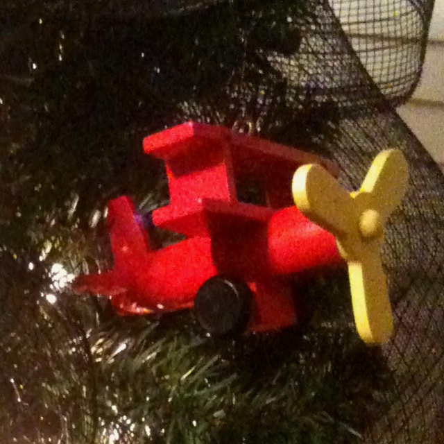 Wooden toys off the dollar aisle at Target...screw in a cheap hook for boys Christmas tree decor!  We used planes, cars, firetrucks, helicopters, trains and multi-colored, vintage inspired C7 lights for a bright inexpensive tree our little man LOVES!