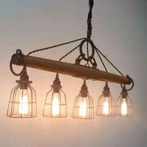 This modern rustic chandelier, featuring five lights, is crafted from a genuine antique single tree yoke. This industrial looking light would look