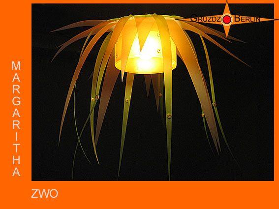 Unsere beliebte Leuchte MARGARITHA, Lichtobjekt in Blütenform, in einer anderen Variante.  Filigran schweben die Blütenblätter um den orangefarbenen Mittelpunkt, der den Raum in sein sanftes Licht taucht.