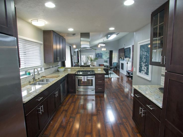 This contemporary kitchen renovation blends dark cabinets and flooring with neutral walls, backsplash and countertops for a polished, sophisticated look. Continuing the wood flooring from living room to kitchen advances the free flow of space from one room to another.