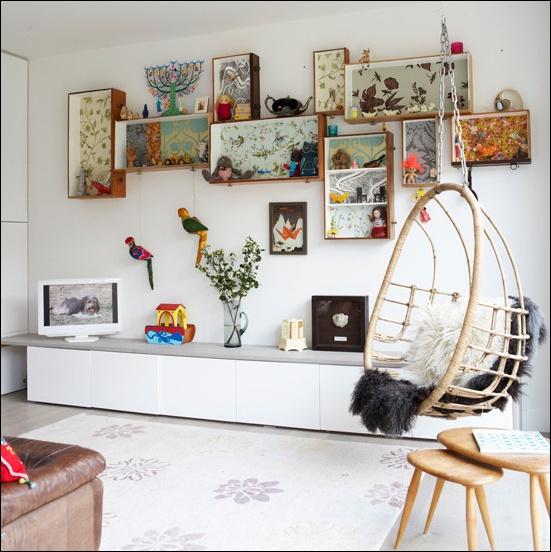 Boven het voeteneinde van het bed komt een collage van ingelijste afbeeldingen en kleine open kastjes met natuurschatten en curiosa. De binnenkant van de kastjes is beplakt met gebloemd behang #IKEAcatalogus