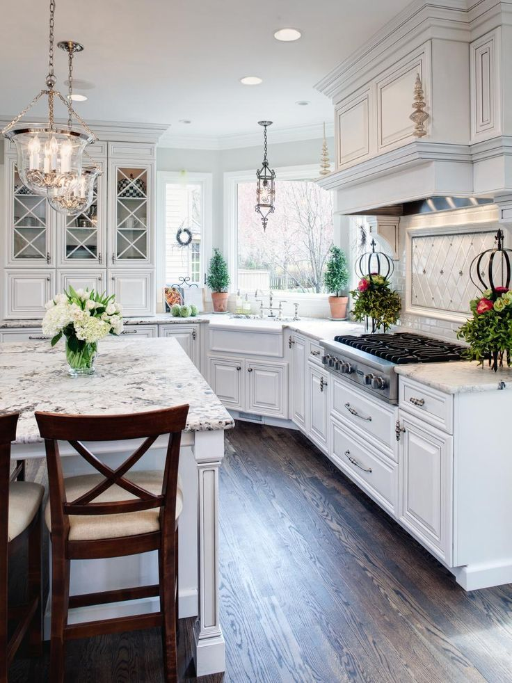 Dark hardwood floors stand out in this all-white kitchen. Glass-front cabinets break up the white cabinets. A white apron sink blends seamlessly with light granite countertops beneath a large picture window. The range hood is disguised as part of the cabinetry above the cooktop. A custom-built island matches the cabinets and countertops, providing a casual dining area.