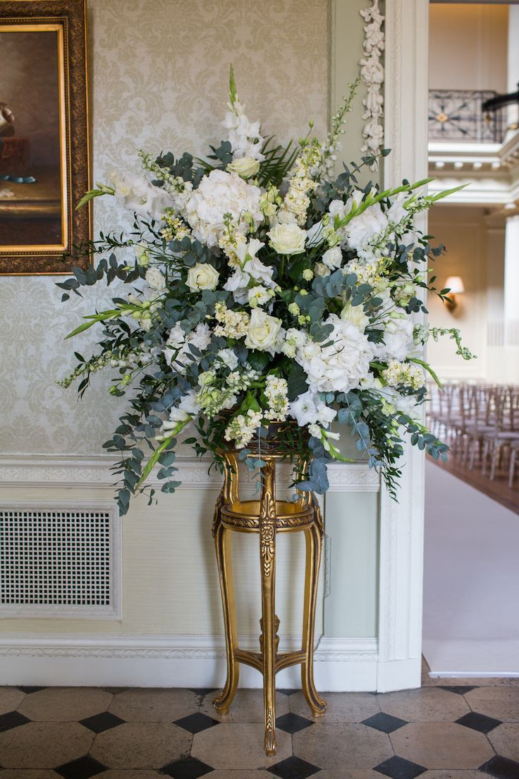 A pedestal of flowers decorating the aisle including White peonies, roses & gypsophila - Image by Mike Garrard - Classic White Wedding At Hedsor House Buckinghamshire With Bride In Augusta Jones Gown With Rachel Simpson Shoes And Bridesmaids In Antique Rose Maids To Measure Gowns With Groom In Bespoke Suit From Gieves And Hawkes Savile Row