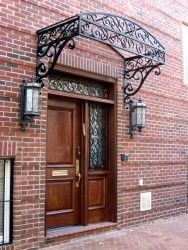 We fabricated an arched glass canopy for the building entrance framed out of wrought iron, plus matching grilles for the transom and window adjacent to the door.