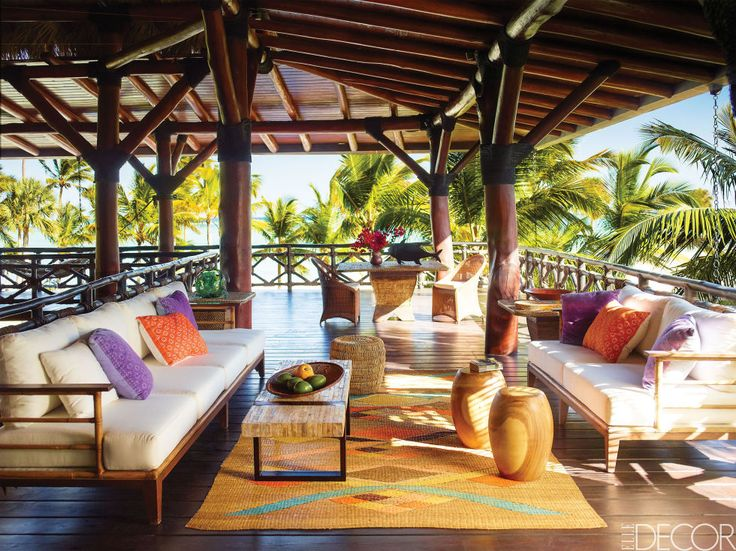 In a Dominican Republic vacation house decorated by Juan Montoya, the upper deck is furnished with sofas strewn with pillows from Mexico. The wood stools and wicker side tables were found locally, and the straw rug is Colombian. Click through for more summer house furniture and summer home decor ideas.