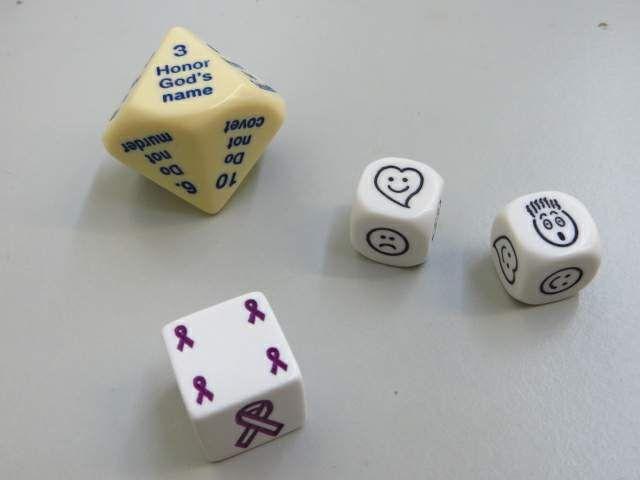 tien geboden, 2 dobbelstenen met emoties en een dobbelsteen met paars lint - staat voor alzheimer. Zoals roze voor strijd tegen borstkanker staat