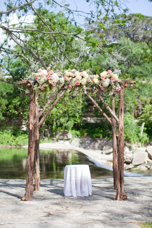 Rustic wedding arch with lush florals in whites and pinks