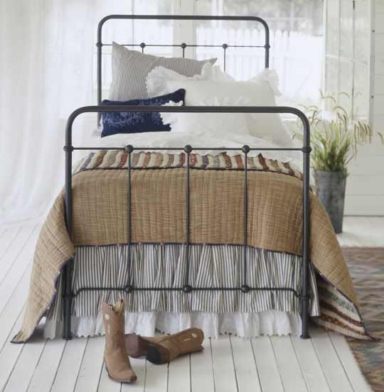 An eyelet dust ruffle plays peek-a-boo under a ticking bed skirt. Layered on a metal bed, a khaki-color quilt is paired with a patchwork quilt made from strips of fabric sewn side-by-side. Pillows and shams made from ticking or eyelet are combined with a stitched throw pillow, giving this bed a perfect Prairie-style look