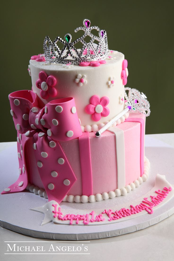 Little Princess #18Milestones This princess cake is two tier and iced in buttercream then decorated with fondant stripes & buttercream daisies. The polka dotted bow is handmade from fondant and delicately placed. A princess tiara and wand top off this royal design.