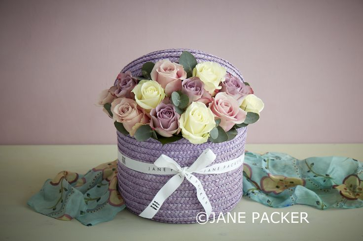 This charming arrangement contains an assortment of delicate Roses in soft violet and blush tones with balmy Eucalyptus strewn throughout, set in floral foam in our dreamy lilac hatbox