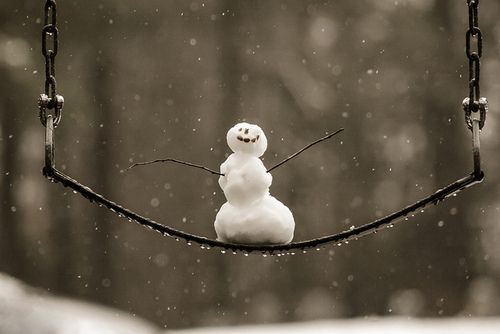 Happy Snowman on a swing with no idea spring is just around the corners his is adorable to me. LMR