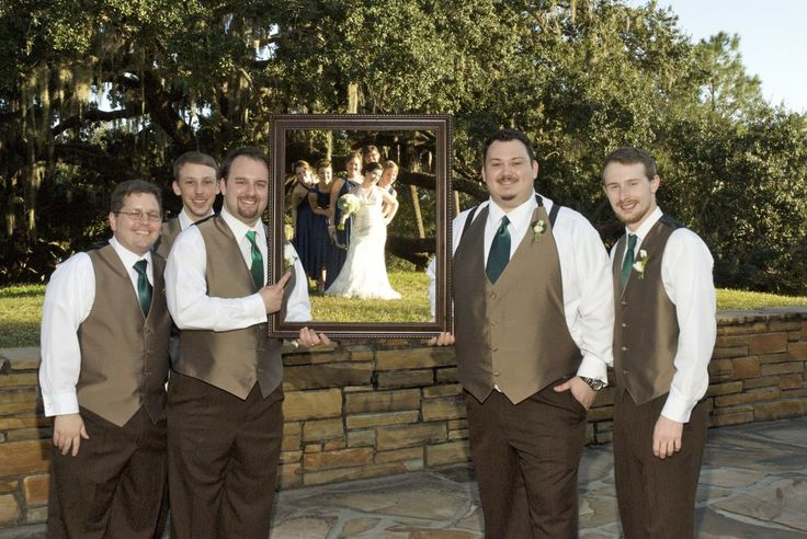 Unique wedding picture of wedding party. Groomsmen holding up picture frame with bride and bridesmaid in it. Pam Minott Photography