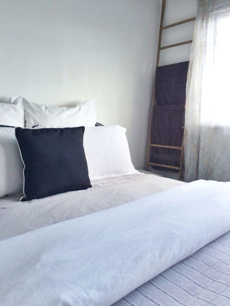 Guest bedroom black and white simple elegant towel ladder inviting