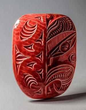 Kāwei Wairua The higher qualities and attributes that we aspire to, to become better human beings  This design brings together two art forms found in a Māori Whare Whakairo (carved house): kowhaiwhai represent genealogy, and the wheku representing a spiritual tipuna (being). As such, this work can represent anyone significant to you. This beautiful work is cast in ceramics from an original wood carving and fired with a range of colourful glazes.