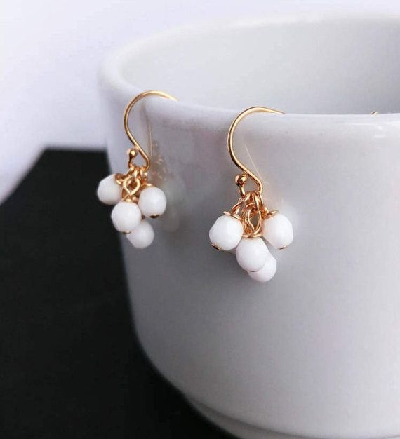 Minimalist pendant cluster earrings with five 4 mm fire-polished white glass pearls and 14k gold filled (or sterling silver) rings and posts. These earrings are modern and luxurious!  Matching necklace: https://www.etsy.com/ca-fr/listing/503854738/collier-or-collier-grappe-or-collier Pink-Coral version: https://www.etsy.com/ca-fr/listing/505936398/boucle-doreille-grappe-argent-boucle Black version: https://www.etsy.com&#x2F...