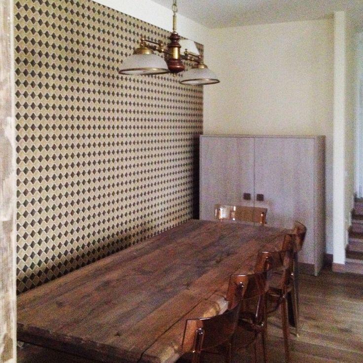 Vista del tavolo in legno con basamento in ferro naturtale cerato e sedie di design contemporaneo, sulla parete retro una carta da parati inglese originale vintage originale anni 80.