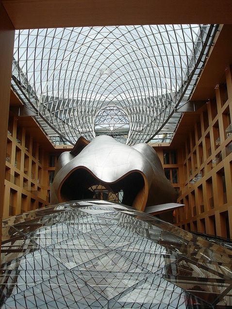 Frank Gehry  sculptural form sheathed in stainless steel  glass covered pathway…