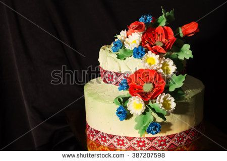 cake in the Ukrainian style with sugar poppies and daisies on  black fabric background