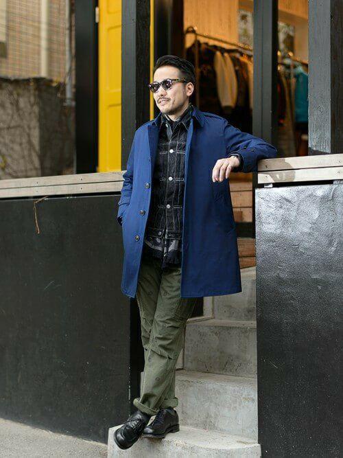 青のステンカラーコートにカーキのコットンパンツ、チェックシャツを組み合わせたコーデ