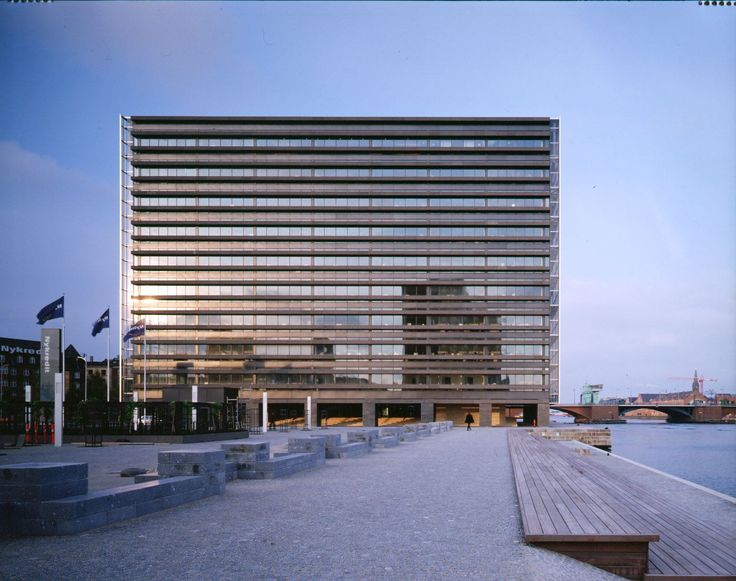 Nykredit Headquarters in Copenhagen (Denmark) where the facades towards the city and the water, respectively, are exclusively made of glass, horizontal ribs of black Chinese granite lend visual weight to the east and west facades – here the west side where wooden stairs and artist Per Kirkeby's stone ornament, in a completely new city space, accentuate the crossing from city to water. #architecture #art #design #copenhagen