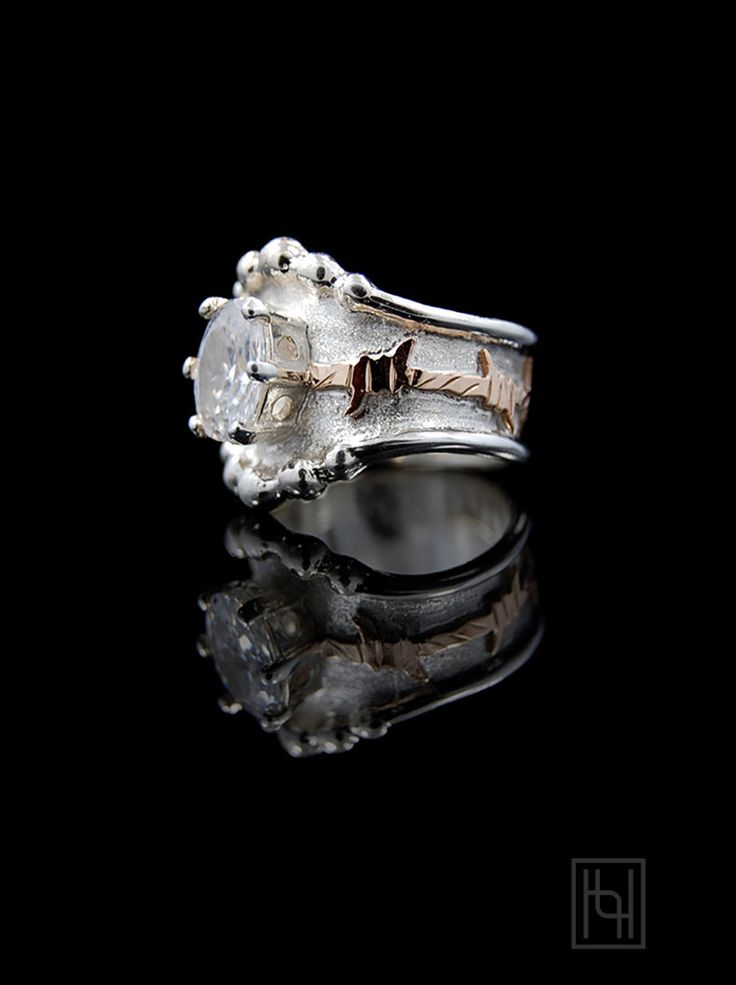 She'll love the flared design and western motif in the Barbed Wire and Oval Crystal Ring!Sterling Silver and 1/10th 10k Yellow Gold.