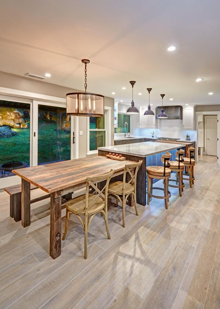 Wood tones warm this eclectic kitchen, which features industrial light fixtures and large windows.