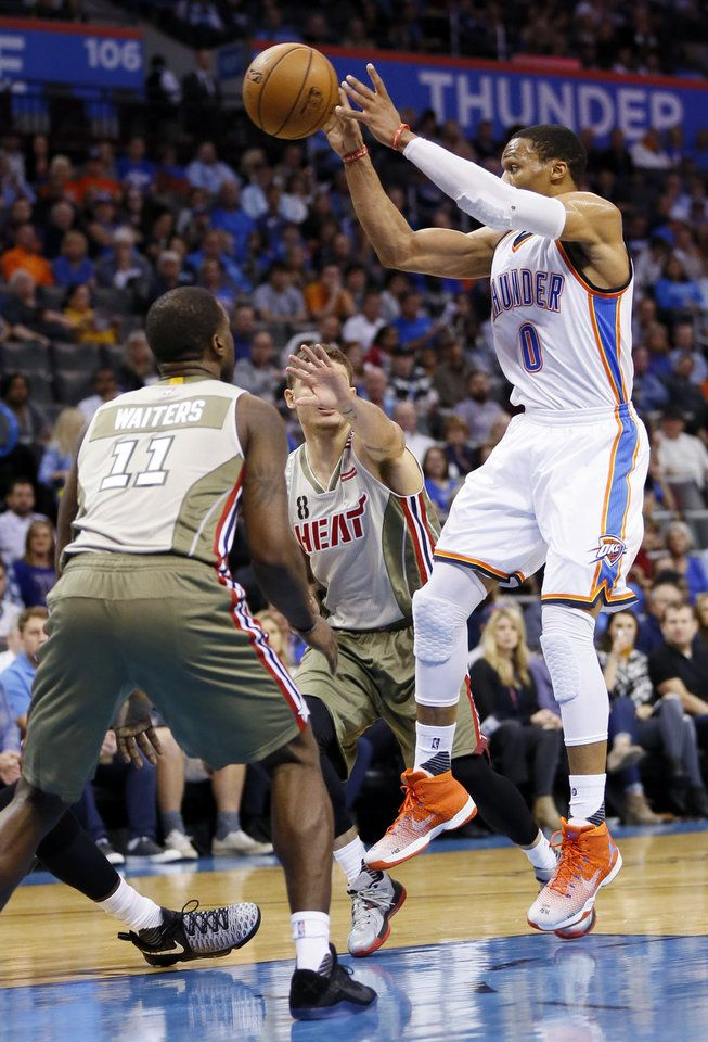 Oklahoma City's Russell Westbrook (0) passes against Miami's Dion Waiters (11) and Tyler Johnson (8) during an NBA basketball game between the Oklahoma City Thunder and the Miami Heat at Chesapeake Energy Arena in Oklahoma City, Monday, Nov. 7, 2016. Photo by Nate Billings, The Oklahoman