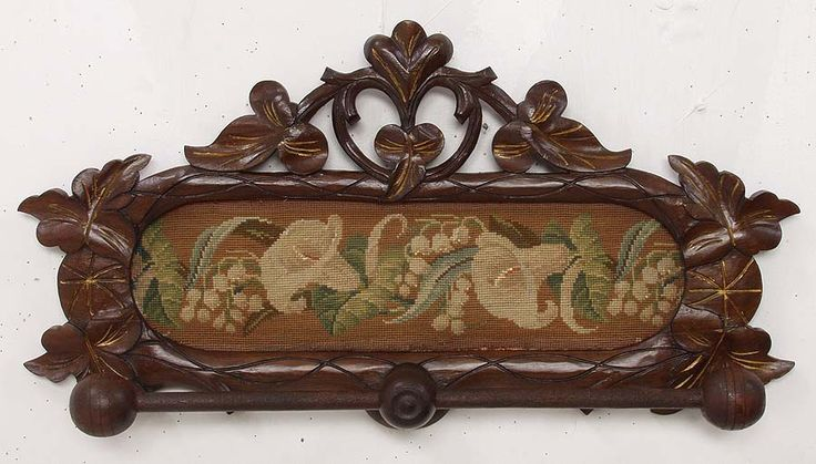 Walnut Victorian towel bar with original inset oval needlepoint design.  The frame features leaf carvings with original gilt incising.  The bar itself has a ball at each end and is held by a center knob.  The needlework features flowers and cherries and is quite intricate