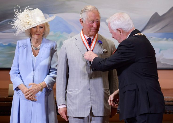 Prince Charles receives the Extraordinary Companion to the Order of Canada medal from Governor General David Johnston as Camilla Duchess of Cornwall looks on at Rideau Hall in Ottawa on Saturday, July 1, 2017. THE CANADIAN PRESS/Adrian Wyld