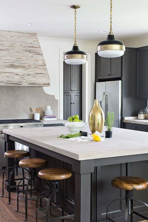 A pecky cypress hood is mounted to a carved gray stone cooktop backsplash fixed above a stainless steel oven range flanked by gray cabinets finished with a gray countertop.