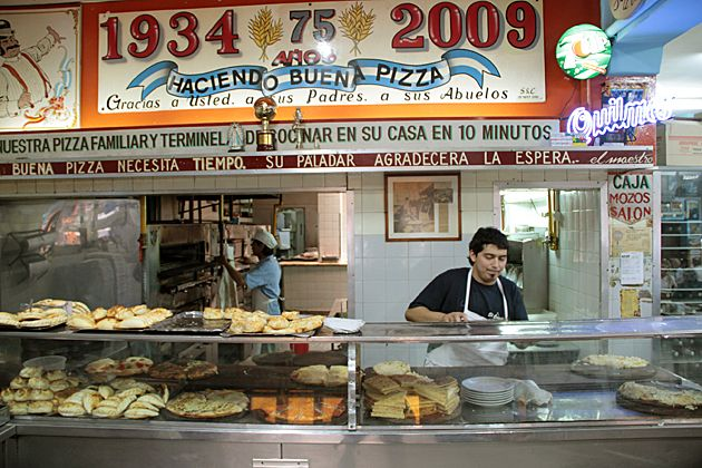 El Cuartito - One of Buenos Aires' oldest and most popular pizzerias. With vintage boxing and football posters covering the walls, a frantic waiter running around the tables to take orders and deliver food. The pizza has a thick dough and much more cheese than a NY slice, but still very tasty. (Pizzeria/Recoleta/Buenos Aires)
