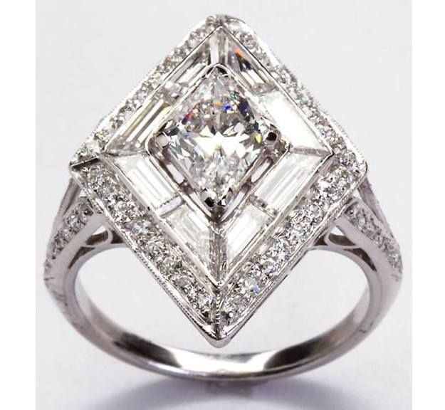 A stunning Art Deco diamond and platinum ring c.1920s/1930s The centre diamond is a lozenge shape brilliant-cut diamond surrounded by calibrated baguette and brilliant diamonds.