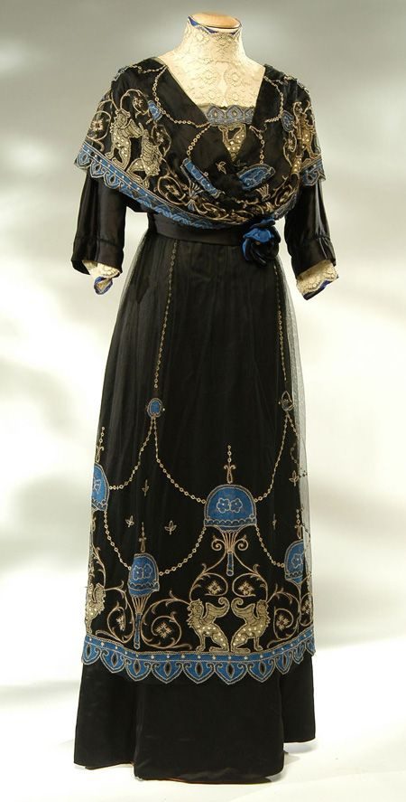 1910 - Whole Dress Satin black silk and tulle embroidered black.    The dress is closed by hooks on the back.The bodice is stiffened by ribs.