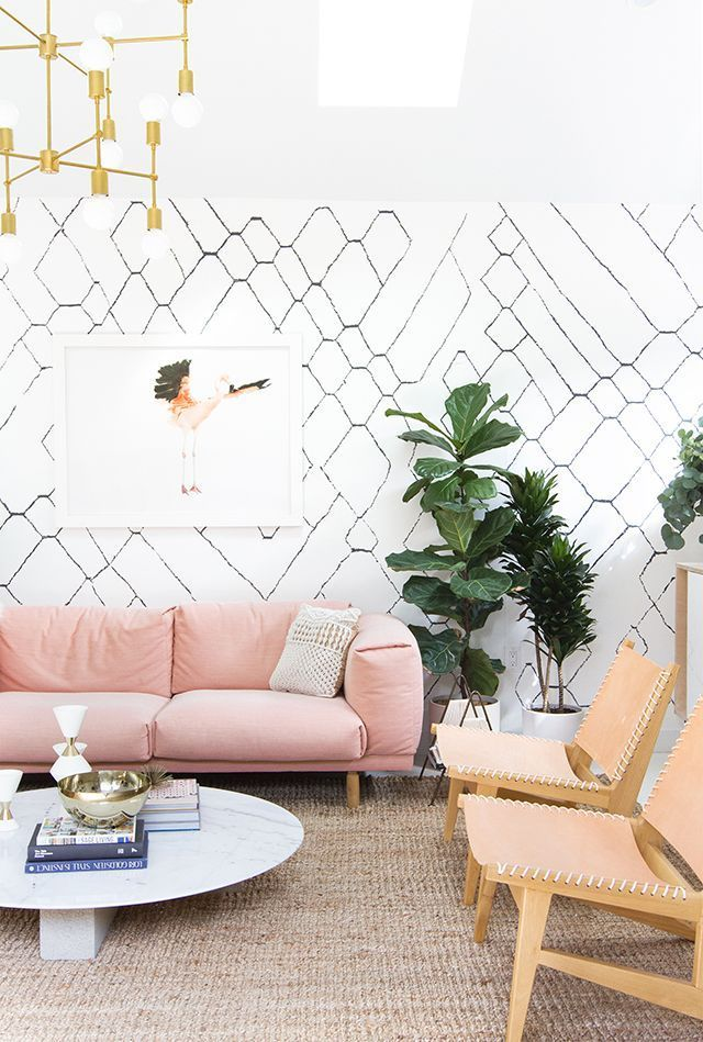 graphic black and white wall paper with pink sofa and tan chairs