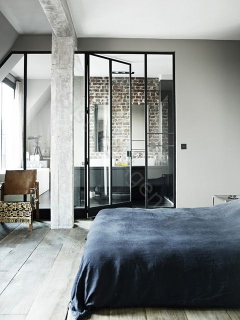 floor to ceiling glass between bedroom and bath. exposed bricks and beams.