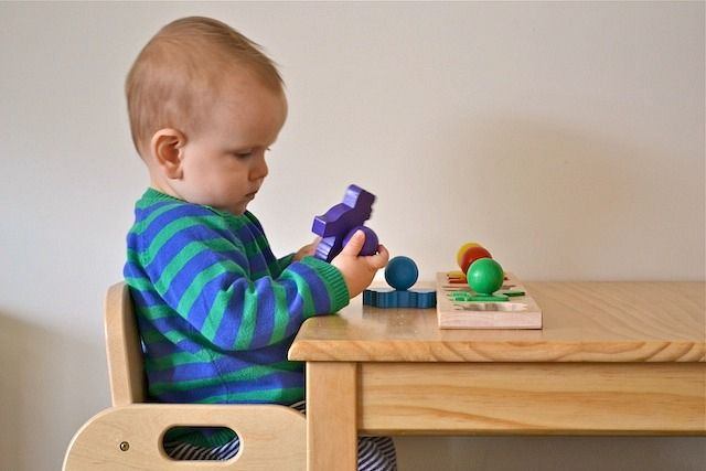 puzzles at a table at 9 months - from how we montessori