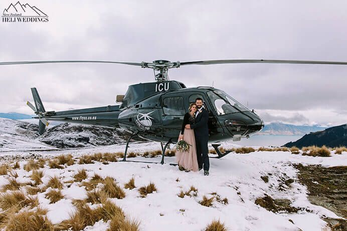 Bride and Groom stand in front of Over The Top Helicopter