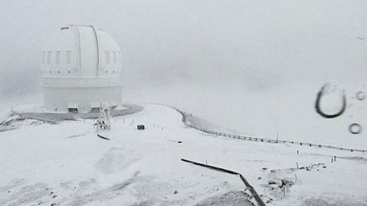 A telescope on the summit of Mauna Kea on Hawaii's Big Island is covered in snow (01 December 2016)