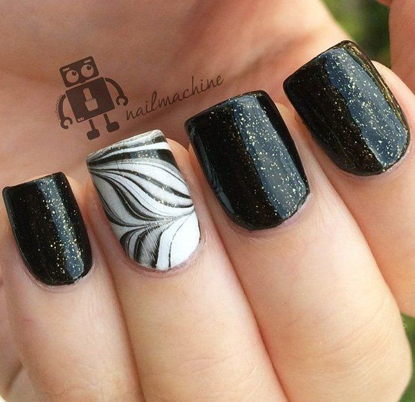 Beautiful black feather nail art design. Combined with a sandwich gold glitter paint design, this nail art combines the soft and elegant touch of the feather and glitter effect. source
