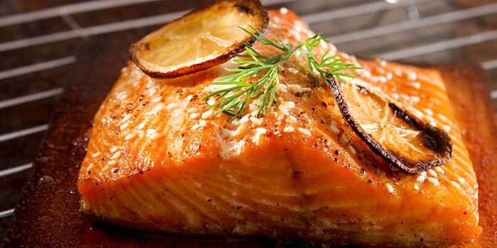 Cooking salmon on cedar planks imparts smoky flavor and protects the fish from sticking to the grill. A maple glaze with ginger adds a touch of sweetness.